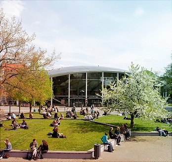 Audimax of the University of Hamburg with blossoming trees and students in the foreground